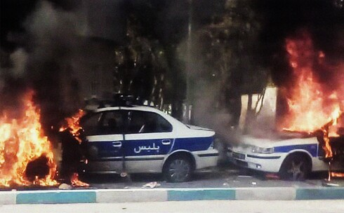 Iranian protesters set fire to police cars during a demonstration against an increase in gasoline prices in Tehran, Nov. 16, 2019