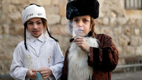 Illustrative: Boys smoke a cigarette in one of Jerusalem's ultra-Orthodox neighborhoods during the Purim festival, March 2018