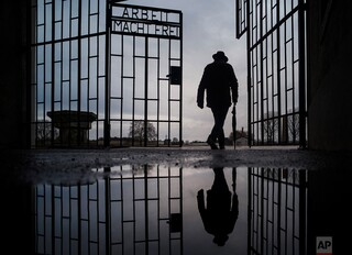 """A man walks through the gate of the Sachsenhausen Nazi death camp with the phrase """"Arbeit macht frei"""" (work sets you free) in Oranienburg, Germany, on International Holocaust Remembrance Day"""