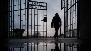 A man walks through the gate of the Sachsenhausen Nazi death camp with the phrase 'Arbeit macht frei' (work sets you free) in Oranienburg, Germany, on International Holocaust Remembrance Day