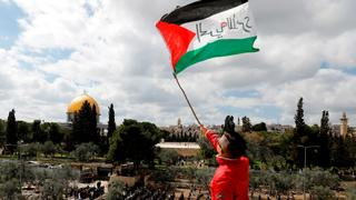 A youth waves the Palestinian flag in East Jerusalem