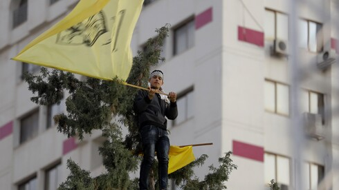 A Palestinian supporter waves a yellow Fatah flag during a celebration marking the 55th anniversary of the Fatah movement in Gaza City, Dec. 31, 2019