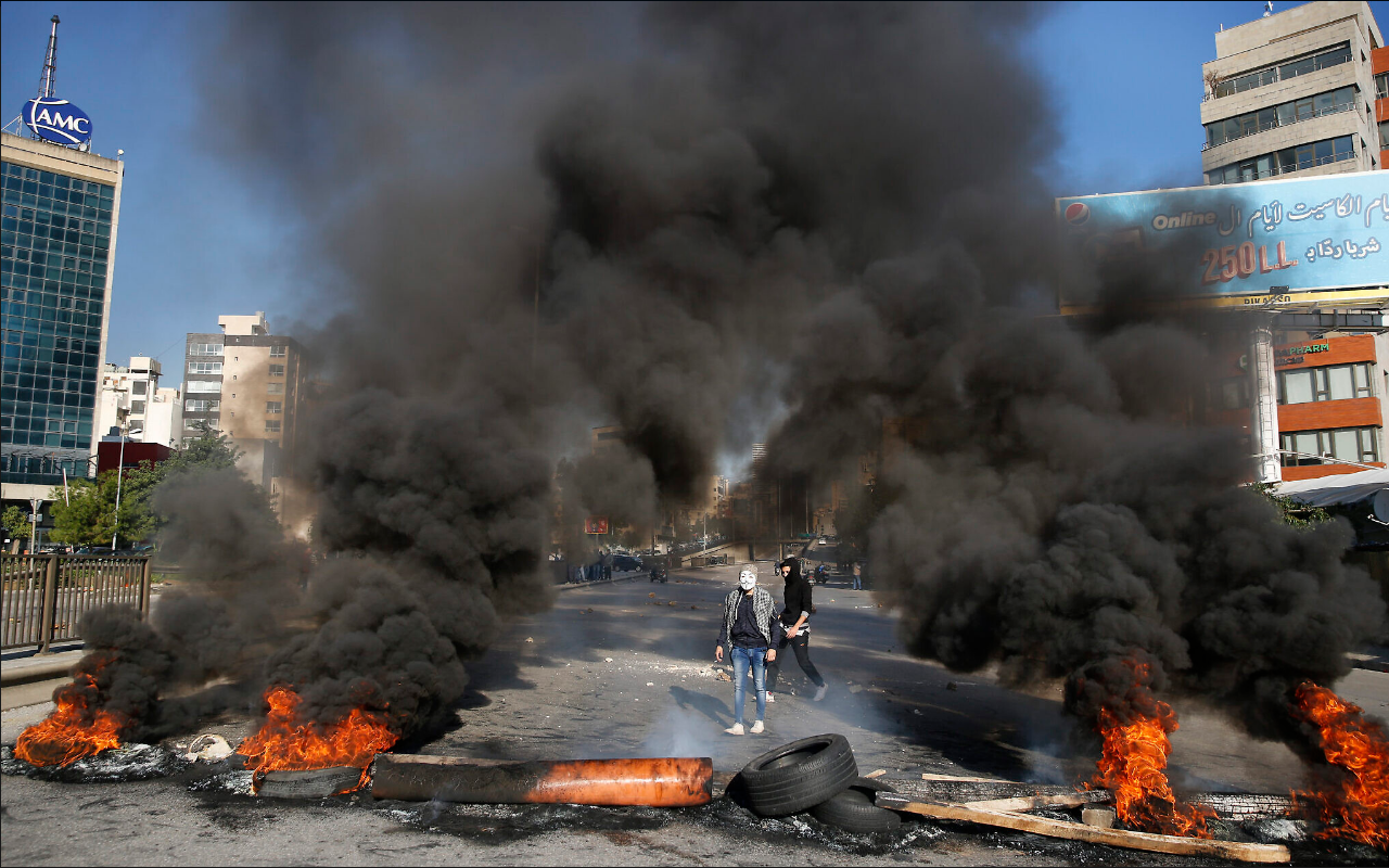Anti-government protesters burn tires during ongoing protests after weeks of calm in Beirut