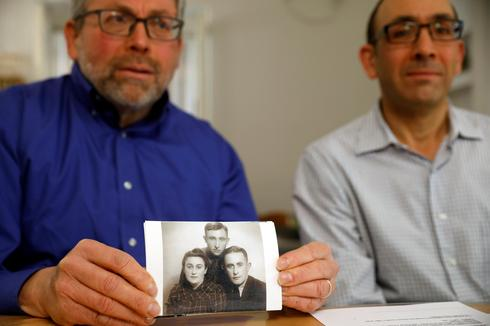 Eli and Saul Lieberman show a photograph of their late father Joseph (top), a survivor of the Nazi death camp Auschwitz, taken several years after the Holocaust