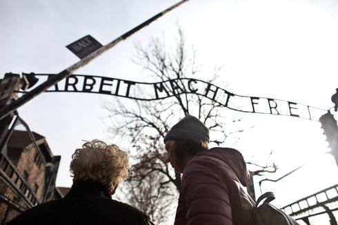 """Jona Laks, survivor of Dr. Josef Mengele's twins experimentsand her granddaughter, Lee Aldar stand next to the gate with the slogan """"Arbeit macht frei"""""""