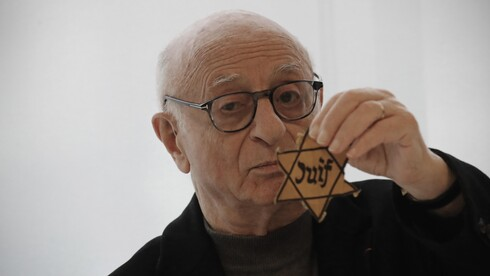 Victor Perahia, who survived the Holocaust as a child, shows a yellow star worn by Jews in Nazi-occupied areas during a workshop at the Drancy Shoah memorial, Jan. 30, 2020