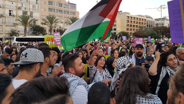 Protesters wave a Palestinian flag during a 2018 demonstration in Tel Aviv's Rabin Square
