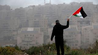 A man waves a Palestinian flag in front of an Israeli settlement in the West Bank