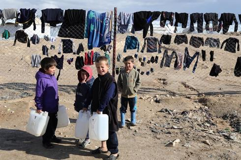 Children hold onto water containers in al-Hol camp