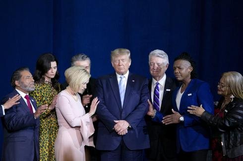 Donald Trump praying in a rally for evangelical voters