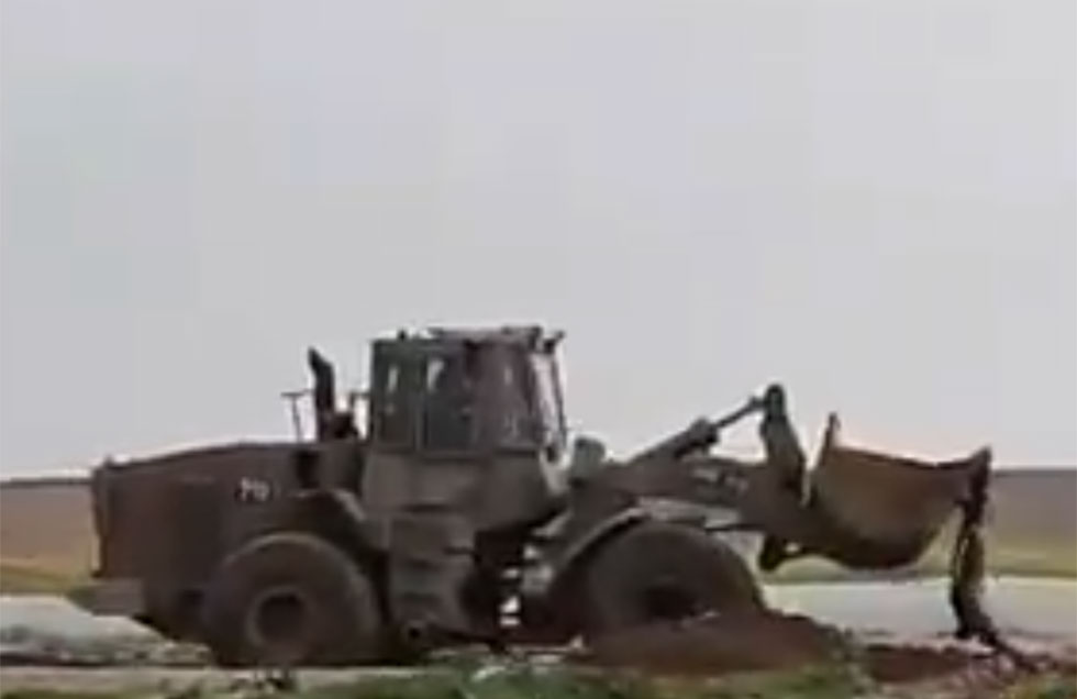 IDF troops drag a militant's body away from the Gaza fence using a bulldozer