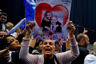 A Likud supporter holds an image of Sara and Benjamin Netanyahu at the party's headquarters on Election Day 2020