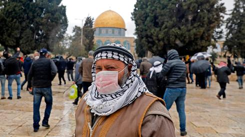 A Muslim worshiper wears a face mask at the Temple Mount in Jerusalem on Friday