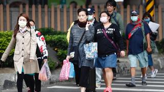 Taiwanese people wearing masks as a precautionary measure walk in the street, in Taipei