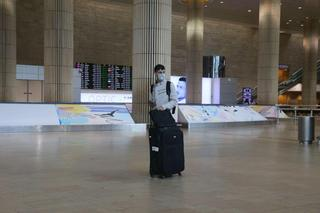 A traveler wears a mask as he arrives at Ben-Gurion Airport, which is now nearly deserted
