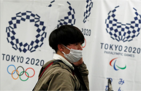 A man in Tokyo wearing a protective mask, walking in front of the IOC offices