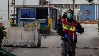 A guard wears a mask against coronavirus at the entrance to Wolfson Hospital in Holon