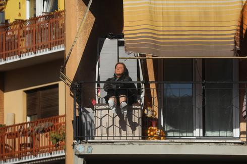 A woman sits on her balcony in Rome during the Italian lockdown