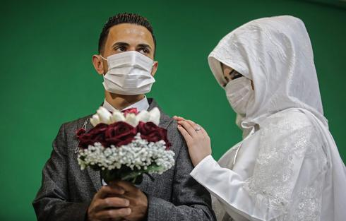 Gaza couple poses for wedding pictures with protective masks due to coronavirus
