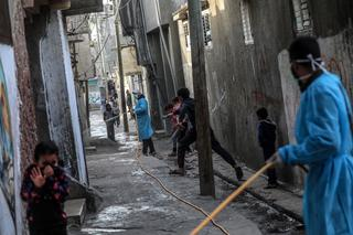 Palestinians spray disinfectant as a precaution against the spread of the Covid-19 coronavirus, in the streets of Al Nusairat refugee camp, central Gaza Strip