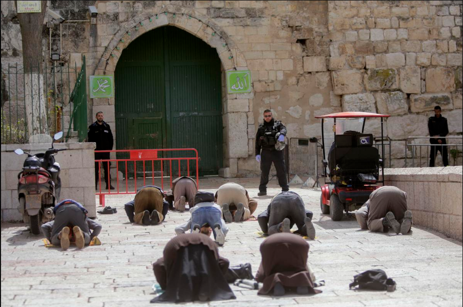 Muslims praying outside the shuttered gates of the Al-Aqsa Mosque