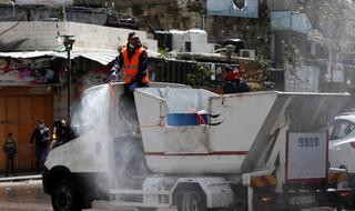 Palestinian municipality employees spray disinfectant in the West Bank town of Hebron, 24 March 2020
