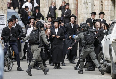 Israeli security forces arrest an Ultra-Orthodox Jewish man as they close a synagogue in the Mea Shearim Ultra-Orthodox neighbourhood in Jerusalem