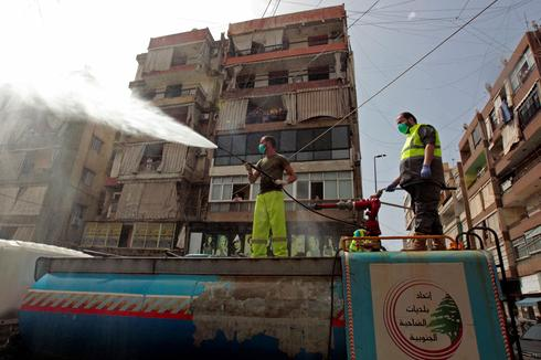 Lebanese sanitation workers spraying disinfectant during coronavirus outbreak