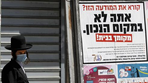 A Bnei Brak resident stands next to a poster urging residents to stay home. 'Reading this notice? You are in the wrong place,' the poster says