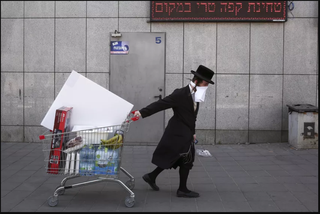An ultra-Orthodox Jew wears an improvised protective face mask as he pulls a supermarket cart in Bnei Brak