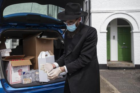 Rabbi Mechel Gancz of from Finchley Chabad in Lodon prepares 'Seder to go' boxes for delivery ahead of the first night of Passover, April 8, 2020