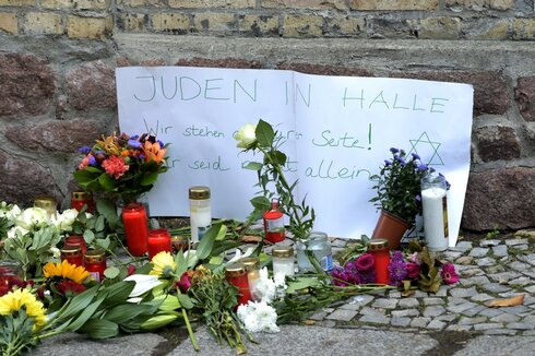 Candles and flowers placed in front of a synagogue in Halle, after a heavily armed assailant ranting about Jews tried to force his way into the synagogue in Germany; Sign reads, 'Jews in Halle - We stay next to you! You are not alone'