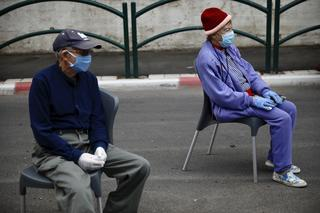 Holocaust survivors Manya Herman, left, and Eliezer Rabinovich wear masks and gloves as they keep a distance while attending an annual Holocaust memorial ceremony