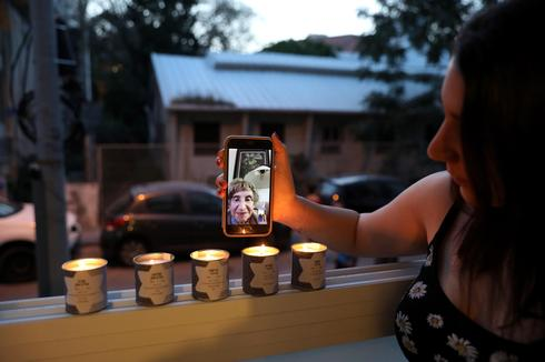 Family member of Holocaust survivor Sonia Perminger (on display), granddaughter Shani Maliniak lights memorial candles in her balcony of her apartment on the eve of Holocaust Remembrance Day