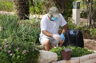 A mourner wearing face mask and gloves visiting grave of loved one in military cemetery during coronavirus outbreak