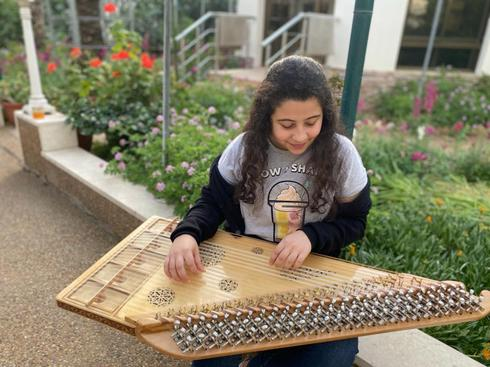 Zaina Alagha playing zither at her house in central Gaza City
