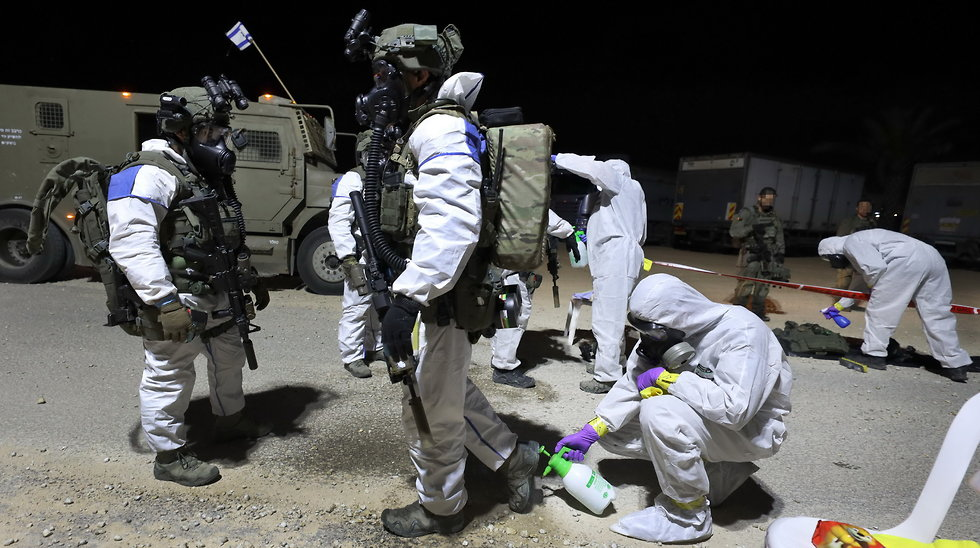 Police anti-terror unit disinfect themselves and their gear ahead of their mission in the West Bank