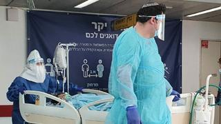 Medics in protective gear against coronavirus with a patient at Ichilov Hospital in Tel Aviv
