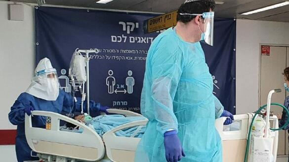 Medics in protective gear with a coronavirus patient a patient at Ichilov Hospital in Tel Aviv
