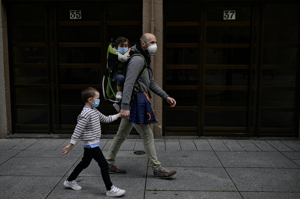 A father with his children wearing face mask to prevent the coronavirus go for a walk at Carlos III promenade, in Pamplona, northern Spain