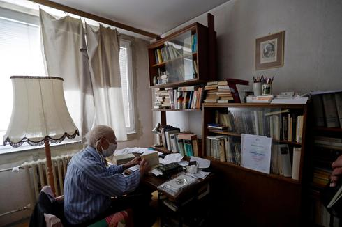 Petr Brandejsky, a 90-year-old Holocaust survivor, reads a book at his apartment during coronavirus outbreak in Prague, Czech Republic