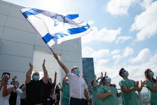 Health workers wave Israeli flags as IAF planes fly over the Ichilov Medical Center in Tel Aviv