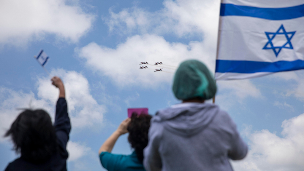 People holding Israeli flags during the Independence Day flyby