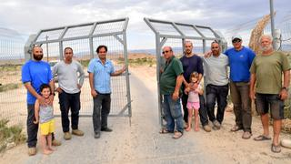 Israeli farmers stand at the gate to the land in Tzofar reclaimed by Jordan