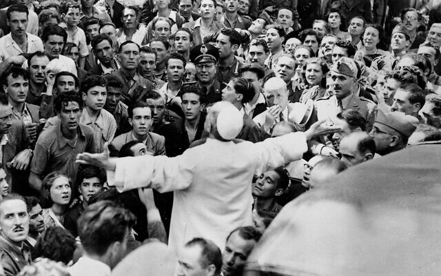 Men, women and soldiers gather around Pope Pius XII, his arms outstretched, on Oct. 15, 1943, during his inspection tour of Rome, Italy