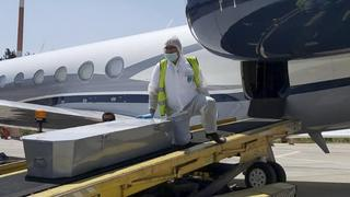 A member of ZAKA voluntary emergency team unloads a coffin from a plane at Ben Gurion airport in Israel