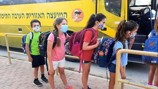 Students boarding a school bus while wearing protective face masks