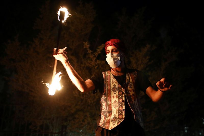 A man plays with fire on a festive Ramadan float as it drives through a street in East Jerusalem to bring celebrations to people under coronavirus disease (COVID-19) movement restrictions