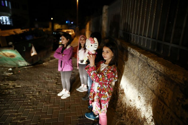 Children watch as a festive Ramadan float drives through a street in East Jerusalem