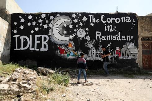 Syrian people stand near a graffiti painted due to the ongoing pandemic of the Covid-19 disease, in Idlib, Syria